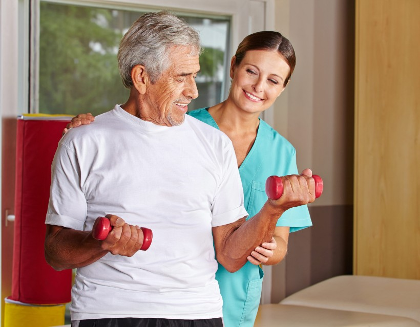 healthcare worker assisting a senior resident with physical therapy