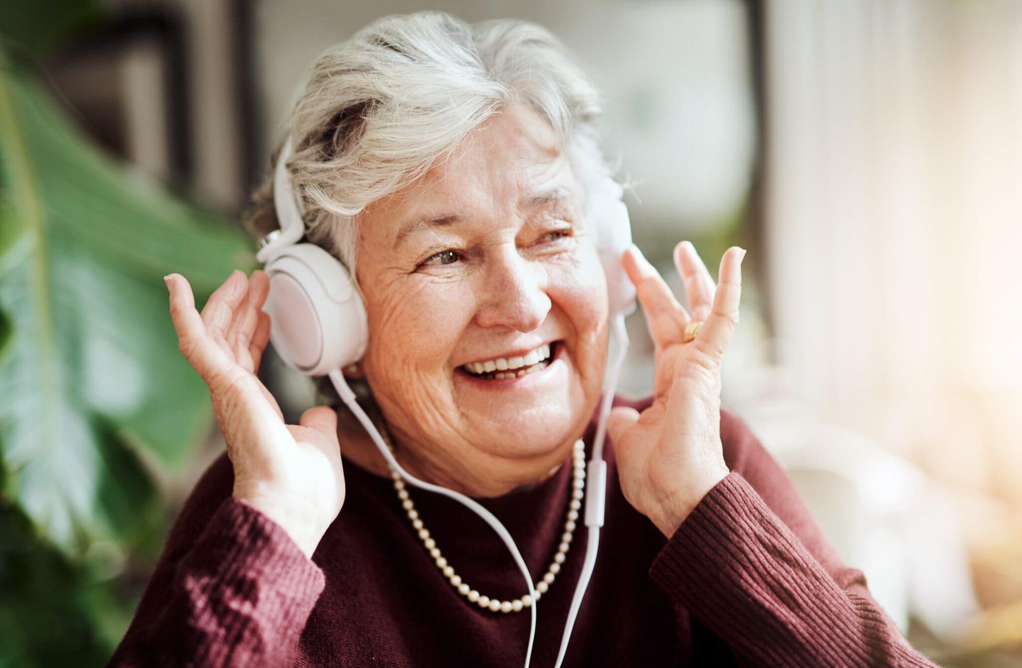 Smiling senior woman listening to music through headphones.