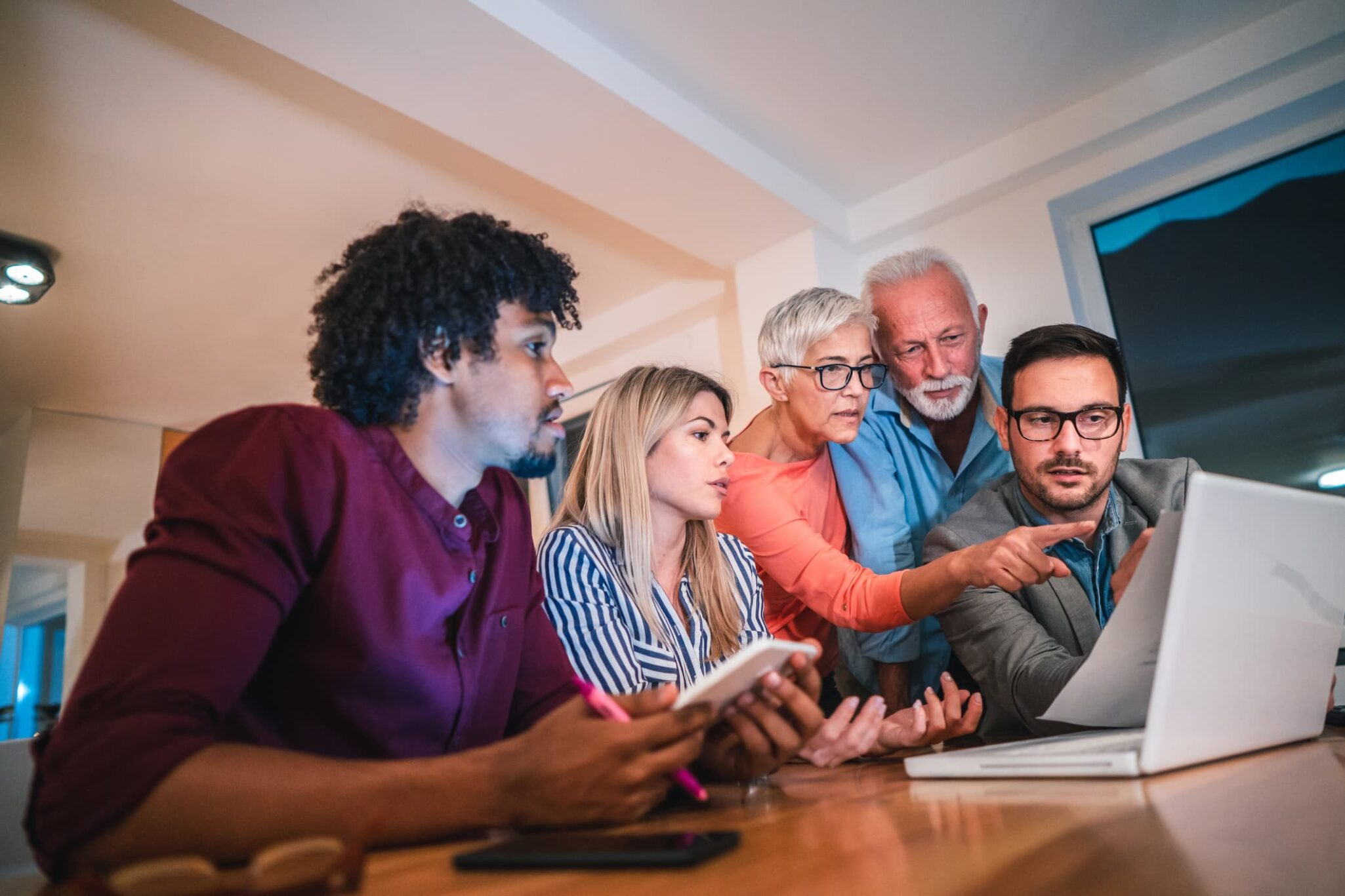 Family consults computer together at dining room table.