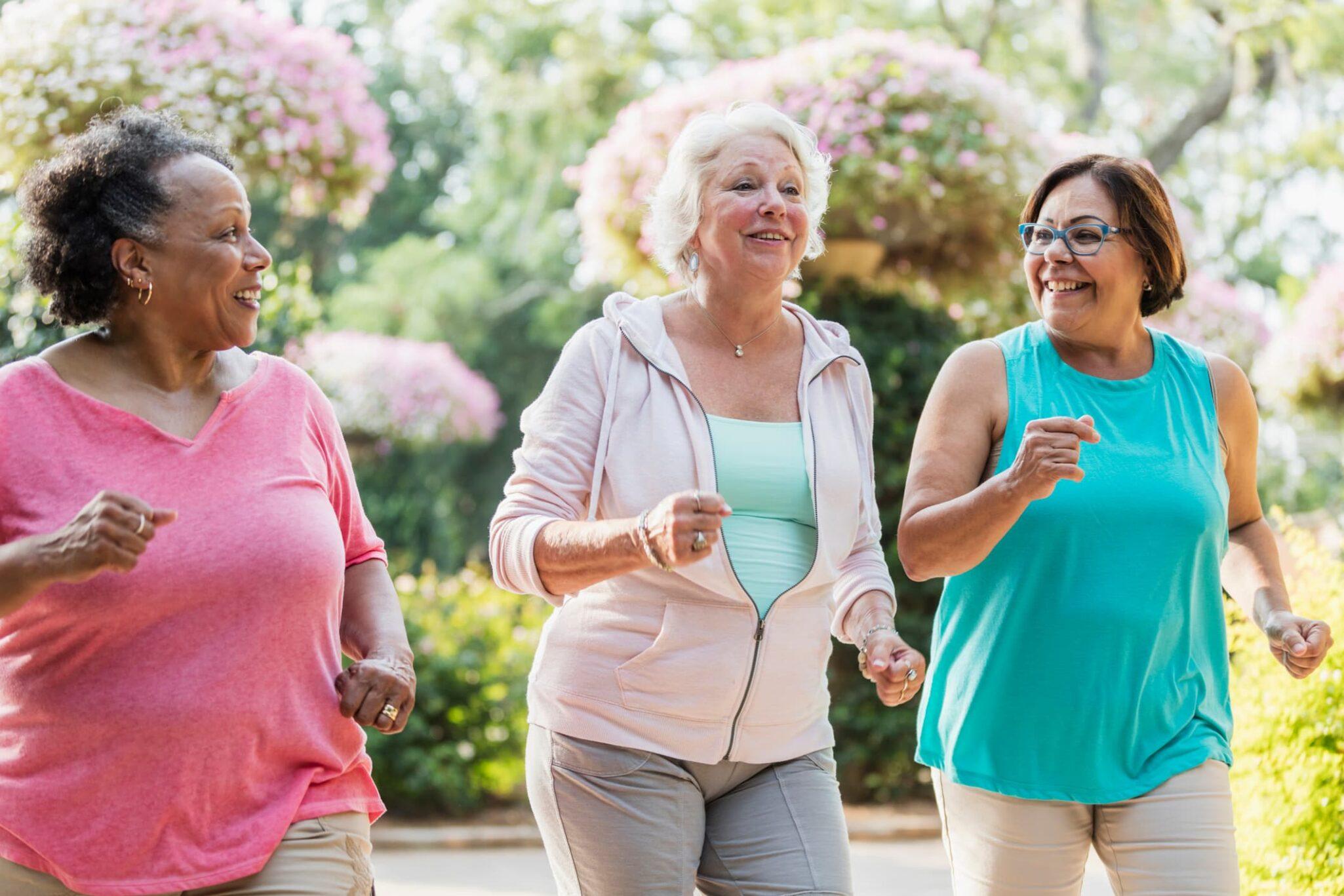 Three older women walking together outside.