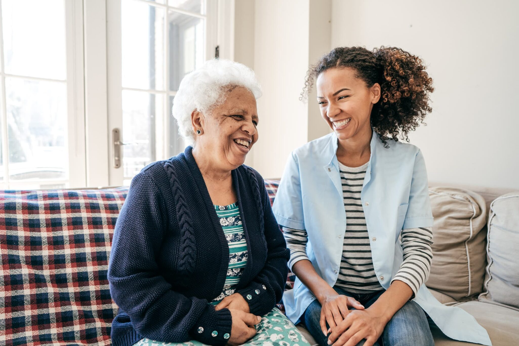 Elderly woman and young female caregiver sitting on couch and laughing.