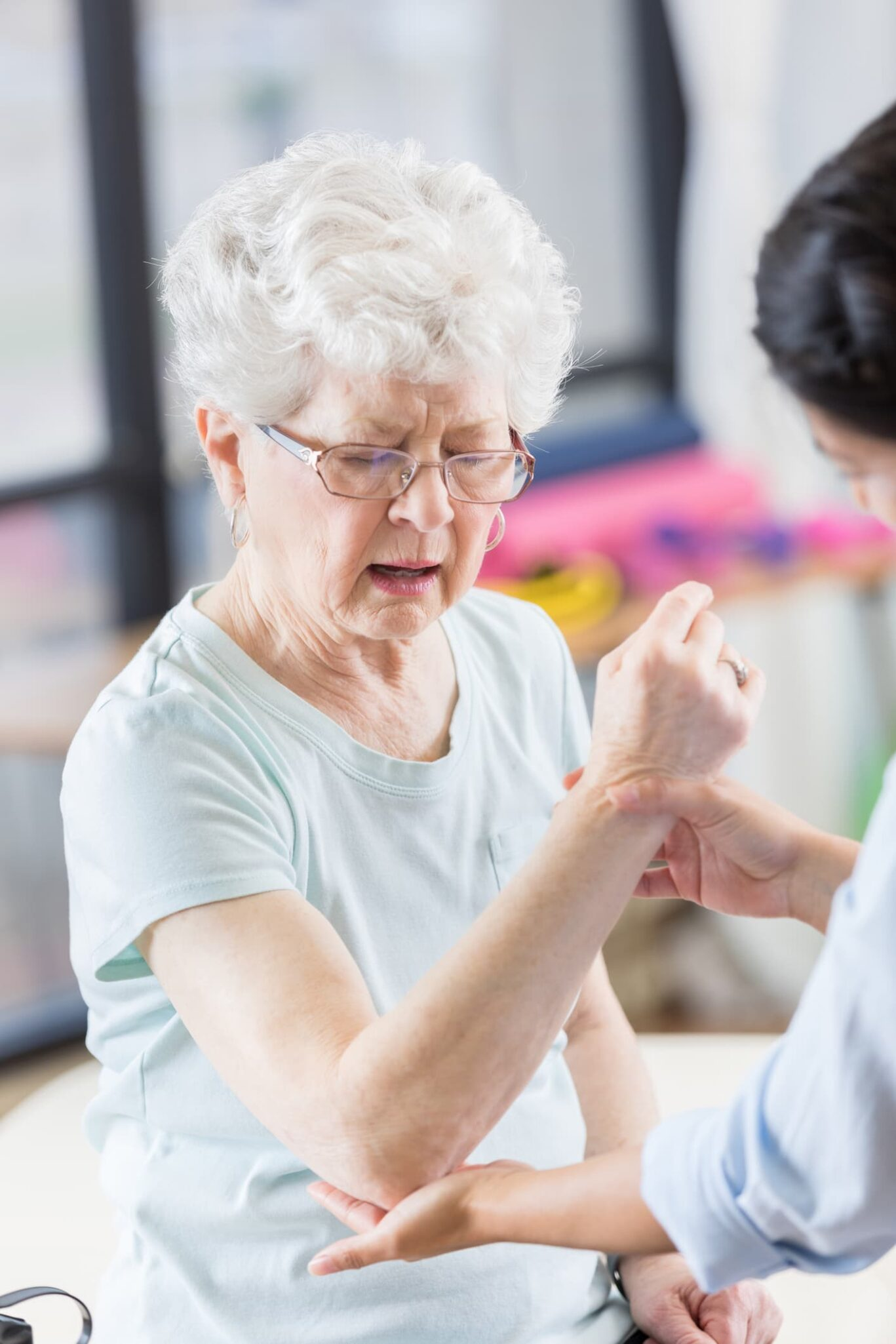 Older woman working on arm range of motion with therapist.