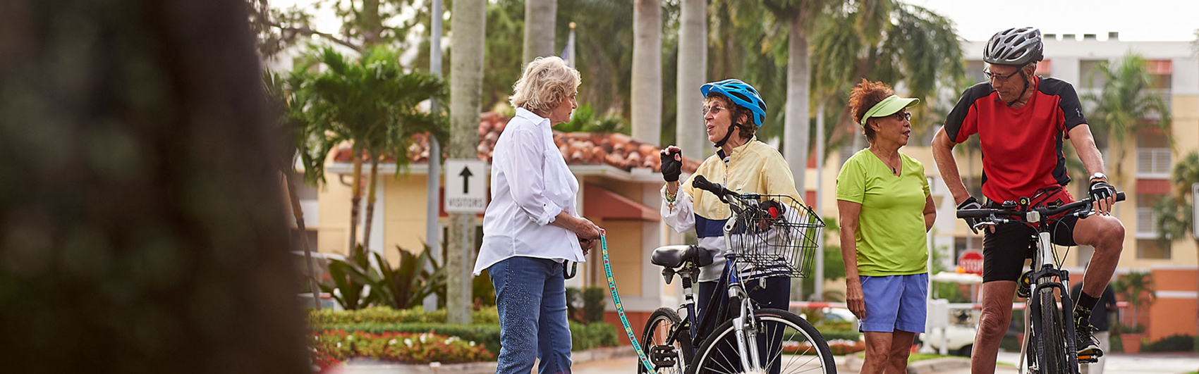 An elderly couple on bikes stopped to speak to two elderly women on a walk